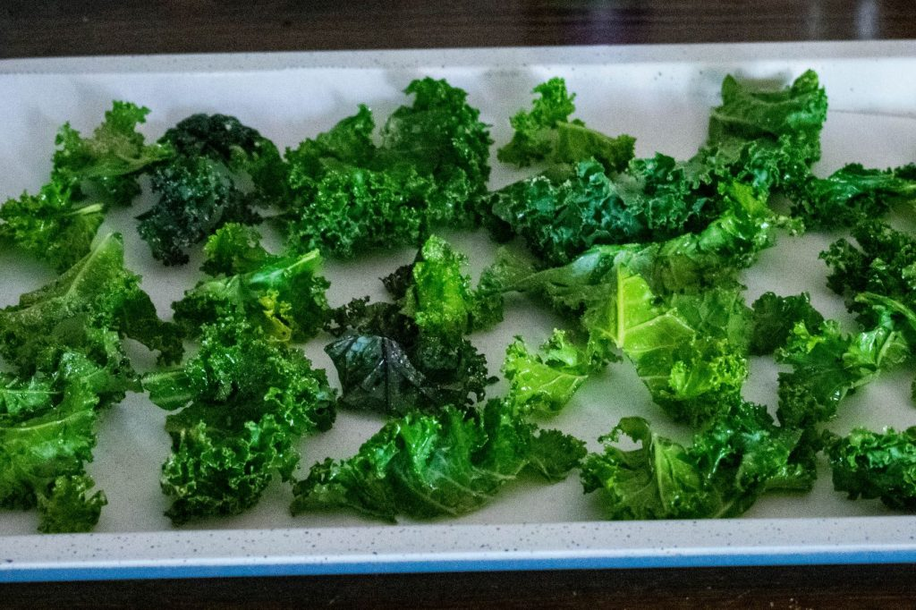 Kale placed on baking sheet ready for oven.