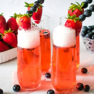 Low-Carb tropical red drinks served in champagne flute.